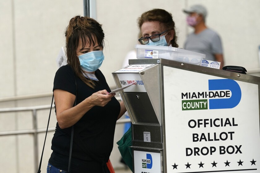 Election worker places mail-in ballot into an official ballot drop box in Miami.