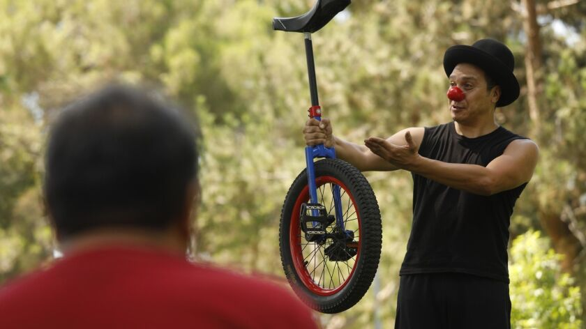 """Professional clown Erick Munias, from Mexico City, Mexico, conducts a workshop Finally, he declared to the roughly 30 people gathered at a park in the city of South Gate: """"I don't want to bore you with text. Let's do something more practical."""" Then he gra"""