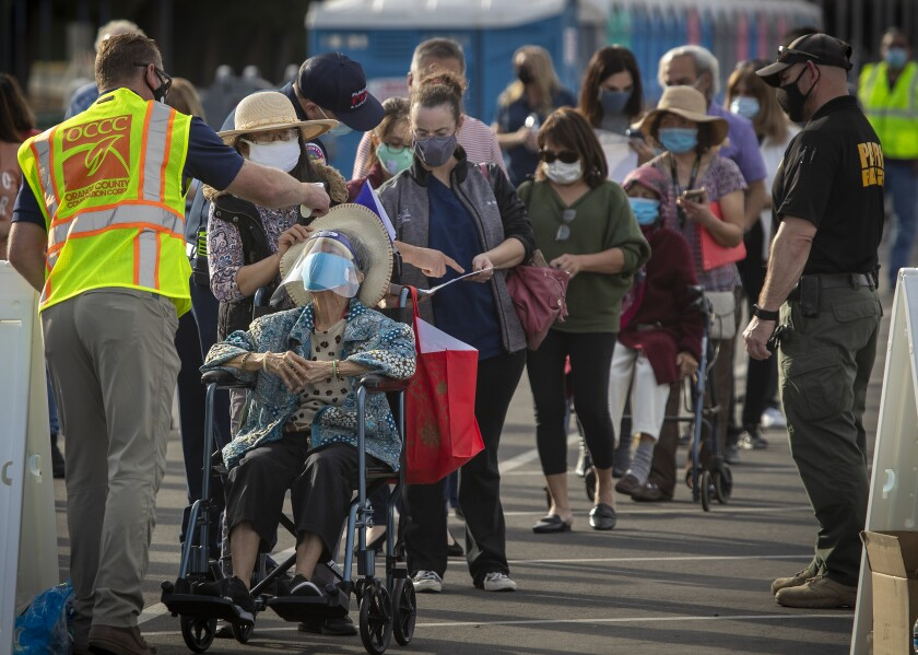 People lined up for the COVID-19 vaccine at Disneyland have their temperatures taken last week.