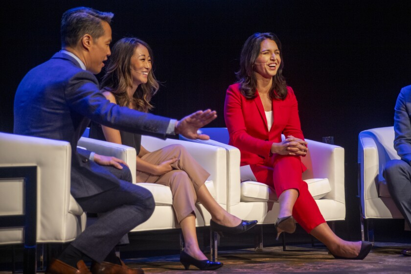 Rep. Tulsi Gabbard (D-Hawaii), in red, speaks Sunday with panelists Richard Lee and Esther Lee at a forum for Democratic presidential candidates at the Segerstrom Center for the Arts in Costa Mesa.