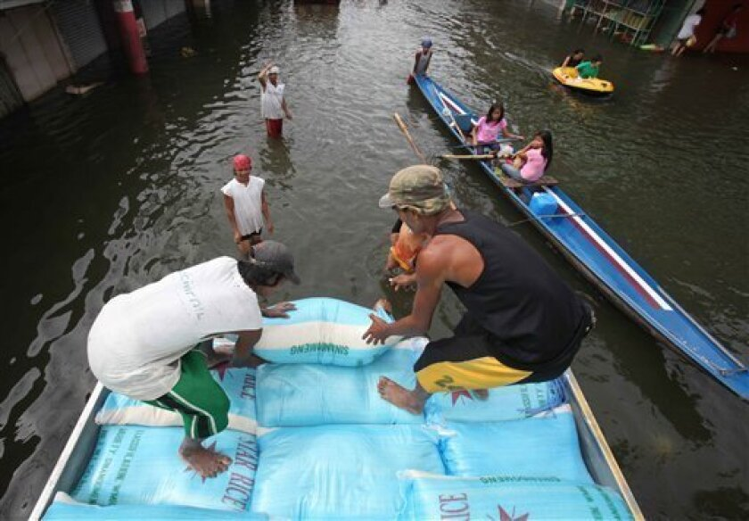 Workers load sacks of rice onto a truck for stockpiling to drier warehouse amidst flooding at Santa Cruz township, Laguna province south of Manila, Philippines Sunday Oct. 4, 2009. Tropical storm Ketsana brought the worst flooding in metropolitan Manila and neighboring provinces in more than 40 years. Landslide buried two families in the Philippines as they sheltered from Asia's latest deadly typhoon which left more than a dozen flooded villages cut off Sunday. (AP Photo/Bullit Marquez)