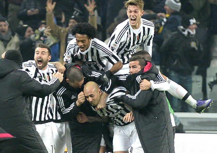 Juventus' Simone Zaza, center, celebrates with is teammates after scoring the winning goal during a Serie A soccer match between Juventus and Napoli at the Juventus stadium, in Turin, Italy, Saturday, Feb. 13, 2016. (AP Photo/Massimo Pinca)