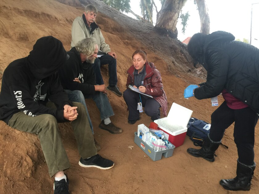 San Diego County public health nurse Aracely Ruvalcaba talks with homeless men.