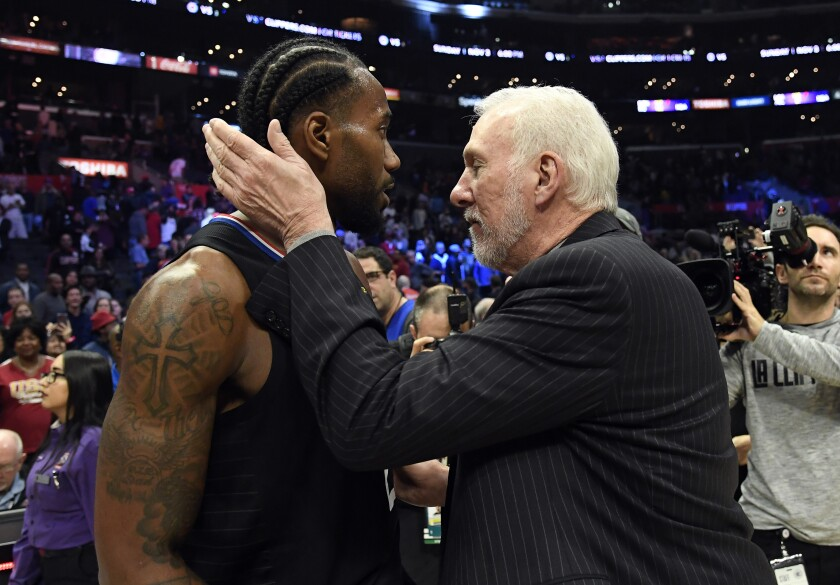 Clippers forward Kawhi Leonard gets a hug from his former head coach, Gregg Popovich, after scoring a game-high 38 points against the Spurs on Thursday at Staples Center.