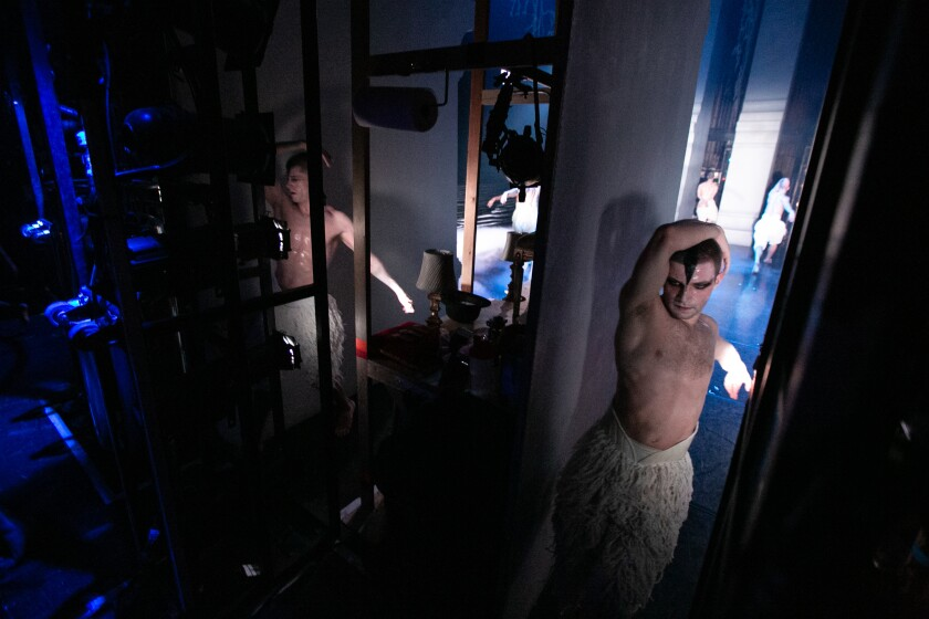 """Dancers exit the stage and thread their way past set pieces tucked in the wings during a matinee of Matthew Bourne's """"Swan Lake"""" at the Ahmanson Theatre."""
