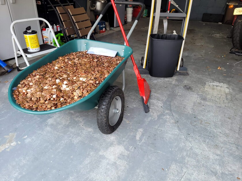 This image provided by Olivia Oxley shows a wheelbarrow filled with pennies, March 20, 2021 in Fayetteville, Ga. A Georgia man said his former employer owed him a pretty penny, $915 to be exact, after leaving his job in November. But Andreas Flaten said he was shocked to see his final payment: 90,000 oil or grease covered pennies, at the end of his driveway earlier this month, news outlets reported. Atop the pile was an envelope with Flaten's final paystub and an explicit parting message. (Olivia Oxley via AP)