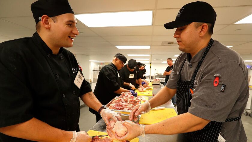 Orlando Ramirez, left, talks with chef instructor Charlie Negrete while breaking down chickens with other students.