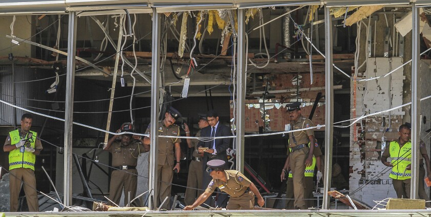 FILE- In this Sunday April 21, 2019, file photo, Sri Lankan police officers inspect the site of an explosion at the Shangri-la hotel in Colombo, Sri Lanka. Sri Lanka has filed 23,270 charges against 25 people in connection with the 2019 Easter Sunday suicide bomb attacks on churches and hotels that killed 269 people, the president's office said Wednesday, Aug. 11, 2021. (AP Photo/Chamila Karunarathne, file)