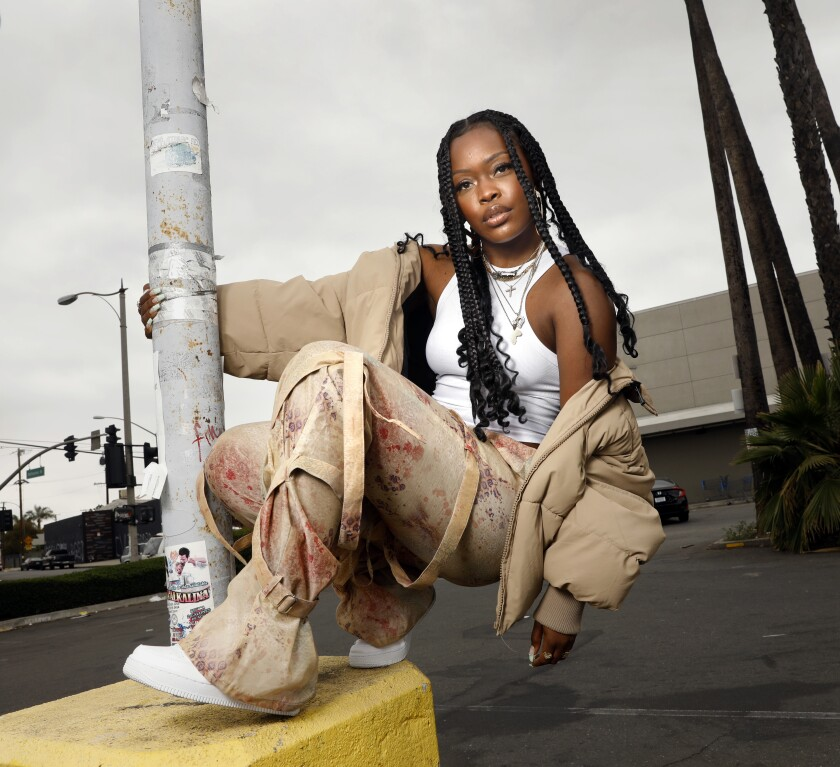 A woman poses on a curb by a pole in a parking lot.