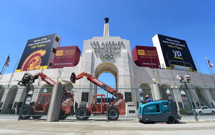A worker manouevers is vehicle past an entrance to the Los Angeles Coliseum, which played host to the 1932 and 1984 Summer Olympics.