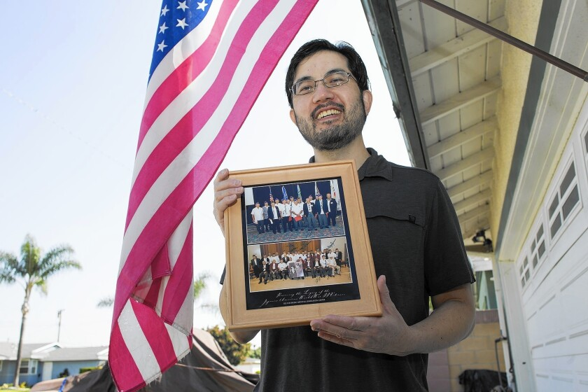 Wayne Osako, 47, of Garden Grove poses with photos of Japanese American WWII veterans he worked with at Go For Broke National Education Center in Los Angeles.