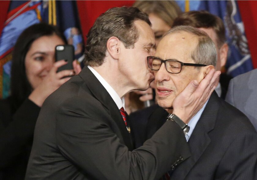 FILE - In this Nov. 4, 2014, file photo, New York Gov. Andrew Cuomo kisses his father, Mario Cuomo, as he celebrates after defeating Republican challenger Rob Astorino, at Democratic election headquarters in New York. Andrew Cuomo is the first New York state Democratic governor since his father to