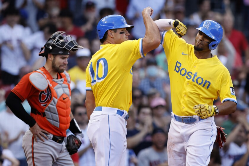 Boston Red Sox's Xander Bogaerts, right, celebrates his three-run home run in front of Baltimore Orioles' Austin Wynns, left, that also drove in Hunter Renfroe (10) during the sixth inning of a baseball game, Saturday, Sept. 18, 2021, in Boston. (AP Photo/Michael Dwyer)