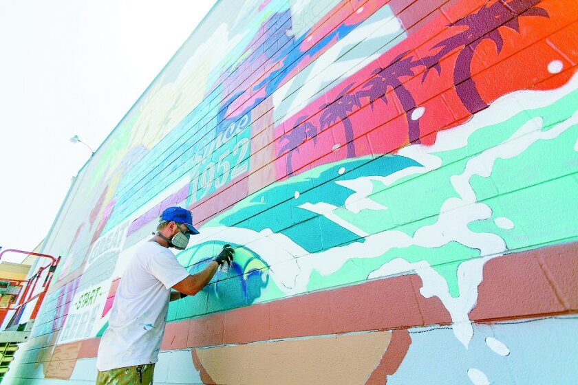 Local artist Skye Walker works on the mural he was commissioned to do by the city of Carlsbad.