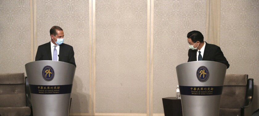 U.S. Health and Human Services Secretary Alex Azar, left, is greeted by Taiwanese Foreign Minister Joseph Wu prior to their meeting in Taipei, Taiwan Tuesday, Aug. 11, 2020. Azar met with Wu on Tuesday during the highest-level visit by an American Cabinet official since the break in formal diplomatic ties between Washington and Taipei in 1979. (AP Photo/Chiang Ying-ying)