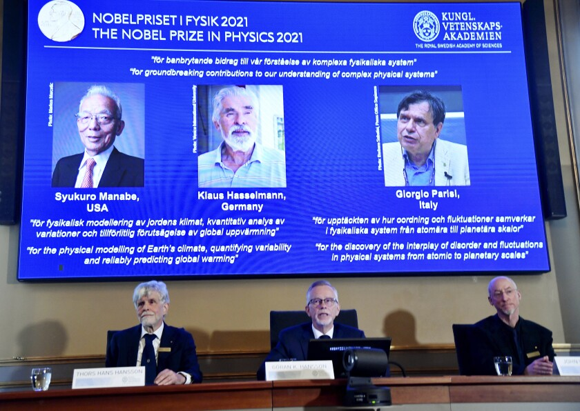 Nobel Committee announcing physics prize with a big screen above them showing winners' photos