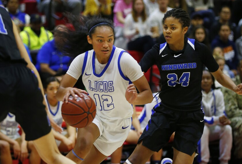 La Jolla Country Day's Te-hina Paopao dribbles between Windward defenders in the Southern California Regional Open Division high school girls basketball championship game. Paopao scored 32 points in the Torreys' win.
