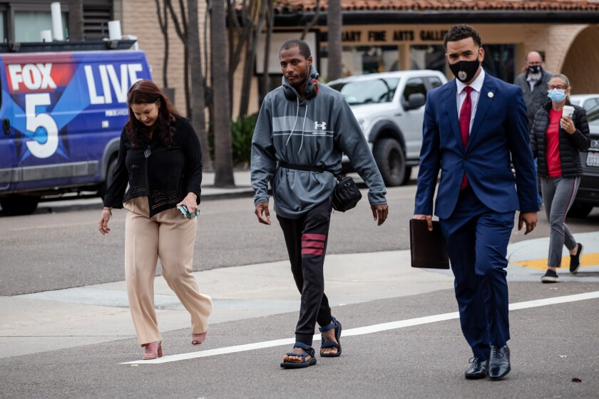 Attorney Marlea Dell'Anno, Jesse Evans, and Shane Harris walk to a news conference in La Jolla on Tuesday, May 18, 2021.