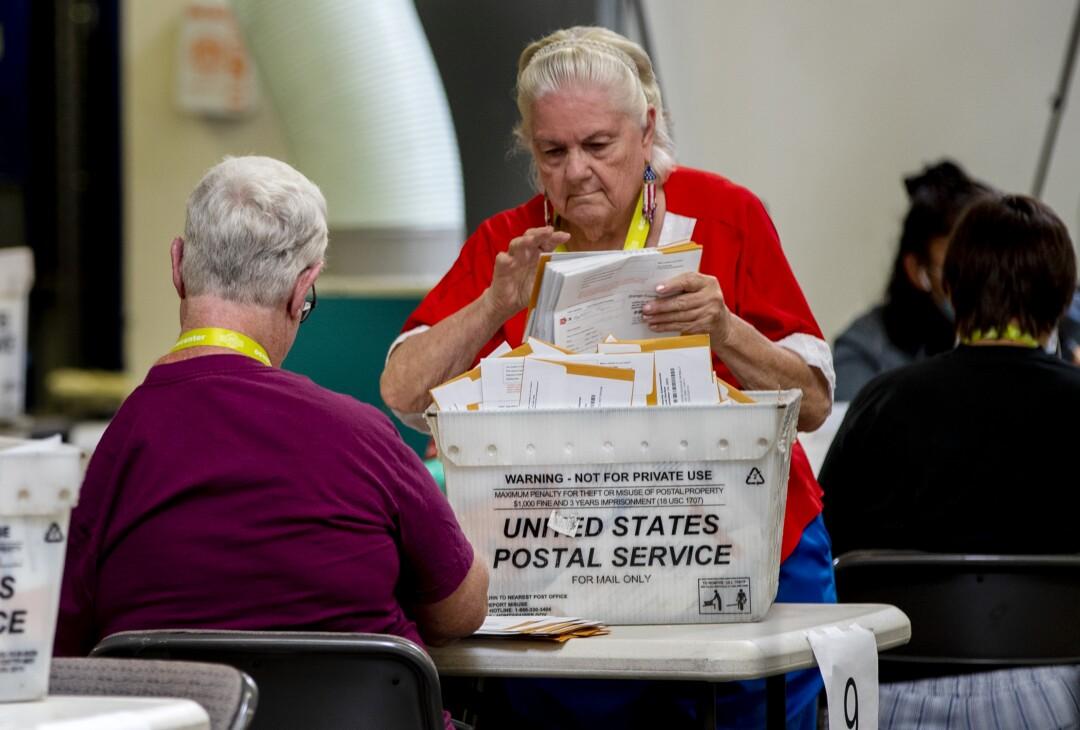 Ein Wahlhelfer mit patriotischen Ohrringen organisiert eingehende Stimmzettel zur Überprüfung