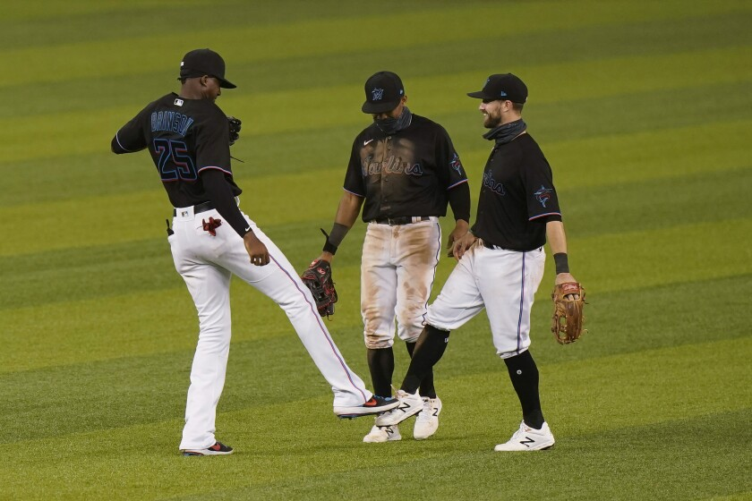 Miami Marlins players Lewis Brinson (25) Magneuris Sierra, center, and Jon Berti celebrate after the Marlins beat the Atlanta Braves 8-2 in a baseball game, Friday, Aug. 14, 2020, in Miami. (AP Photo/Wilfredo Lee)