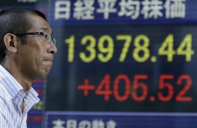 A man walks past an electronic stock indicator showing Japan's benchmark Nikkei Index gained 405.52 points, or 2.99 percent, to close at 13,978.44 for the day in Tokyo, Tuesday, Sept. 3, 2013. Asian stock markets advanced Tuesday after the likelihood of an imminent U.S.-led attack against Syria faded and manufacturing rebounded in China and parts of Europe. (AP Photo/Shizuo Kambayashi)