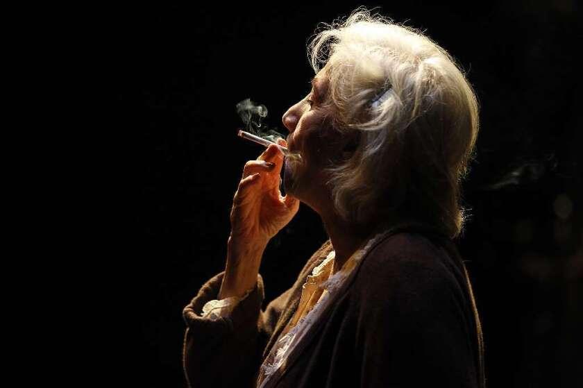 Olympia Dukakis fuma un cigarrillo.
