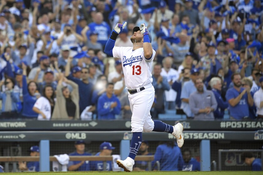 FILE- In this Oct. 9, 2019, file photo, Los Angeles Dodgers' Max Muncy celebrates his two-run home run against the Washington Nationals during the first inning in Game 5 of a baseball National League Division Series in Los Angeles. Muncy and the Dodgers agreed to a $26 million, three-year contract Thursday, Feb. 6, 2020, and avoided salary arbitration. (AP Photo/Mark J. Terrill, File)