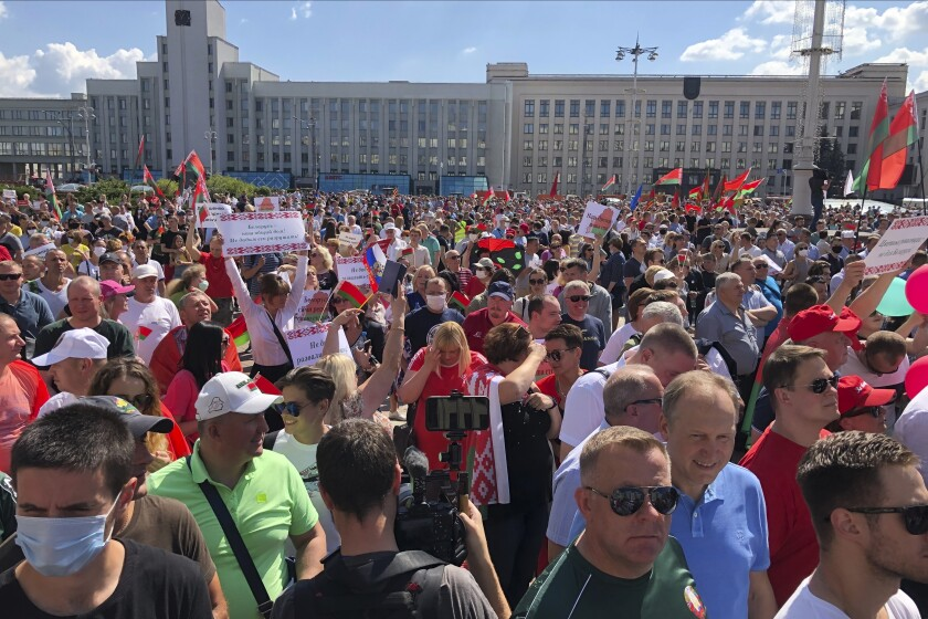 """Hundreds of supporters of Belarusian President Alexander Lukashenko with Belarusian State flags, and a poster that reads: """"Our President, our Country!, Not let destroy the country"""", gather at Independent Square of Minsk, Belarus, Sunday, Aug. 16, 2020. On Saturday, thousands of demonstrators rallied at the spot in Belarus' capital where a protester died in clashes with police, calling for Lukashenko to resign. (AP Photo/Sergei Grits)"""