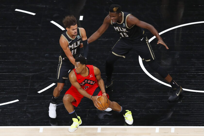 Toronto Raptors guard Kyle Lowry (7) is defended by Atlanta Hawks' Trae Young (11) and and Clint Capela (15) during the first half of an NBA basketball game Saturday, Feb. 6, 2021, in Atlanta. (AP Photo/Todd Kirkland)