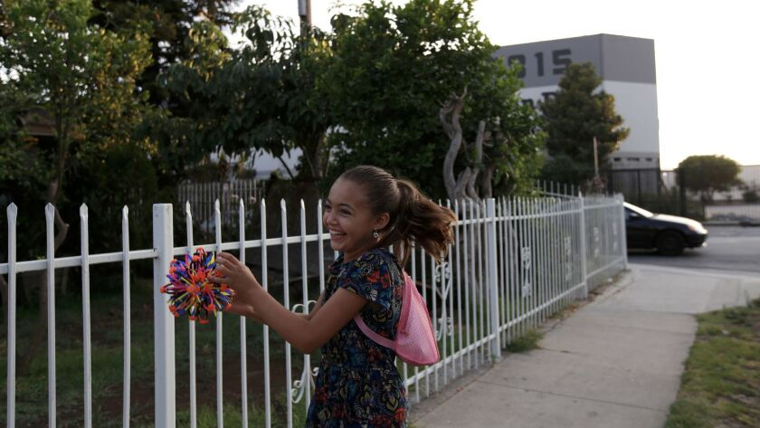 Bella Marquez, 8, plays catch across the street from Maywood L'Chaim, the second business that was approved for licenses to cultivate, manufacture and dispense marijuana.