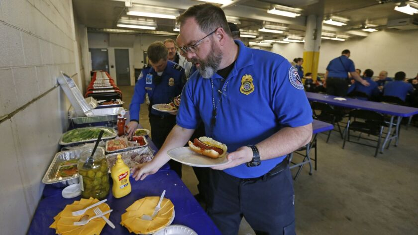 TSA employee Gary Vetterli prepares a hot dog during lunch at Salt Lake City International Airport,