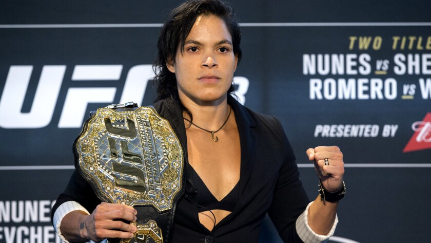 Amanda Nunes strikes a pose with her bantamweight belt over her shoulder during media day for UFC 213 on Thursday.