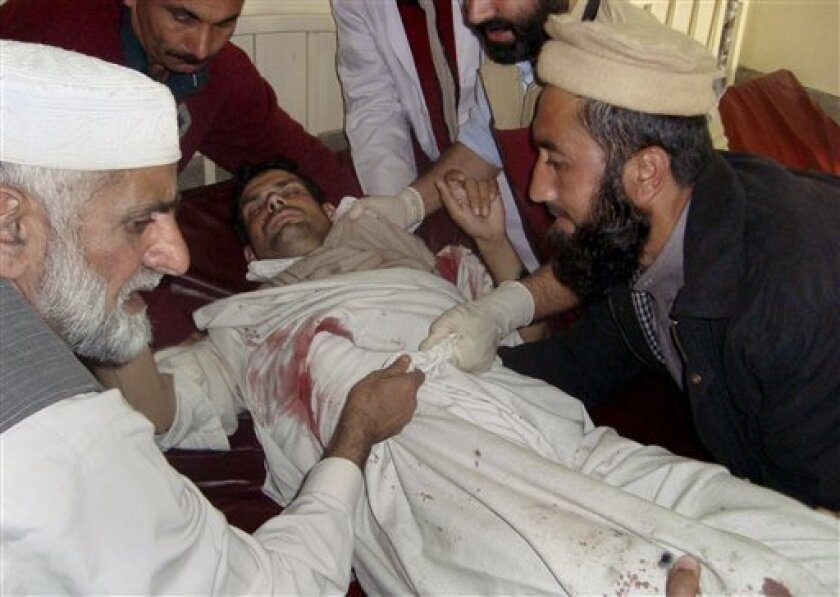 Relative and paramedics shift an injured victim of a suicide bombing into the bed at a local hospital in Saidu Sharif, a town of Pakistan's Swat Valley, Tuesday, Dec. 1, 2009. A teenage suicide bomber killed an anti-Taliban lawmaker in his house in Pakistan's Swat Valley, showing the militant threat in the region remains months after a military push there was declared a success. (AP Photo/Naveed Ali)