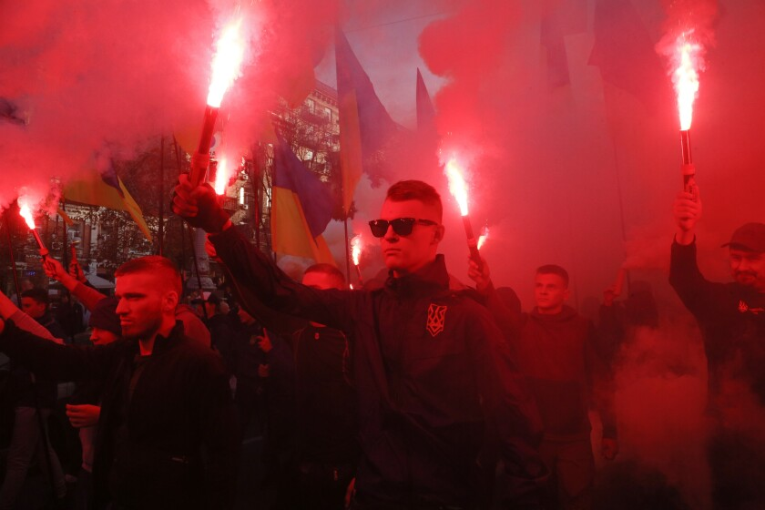 "Members of the nationalist movements light flares during a rally marking Defense of the Homeland Day in center Kyiv, Ukraine, Monday, Oct. 14, 2019. Some 15,000 far-right and nationalist activists protested in the Ukrainian capital, chanting ""Glory to Ukraine"" and waving yellow and blue flags. President Volodymyr Zelenskiy urged participants to avoid violence and warned of potential ""provocations"" from those who want to stoke chaos. (AP Photo/Efrem Lukatsky)"