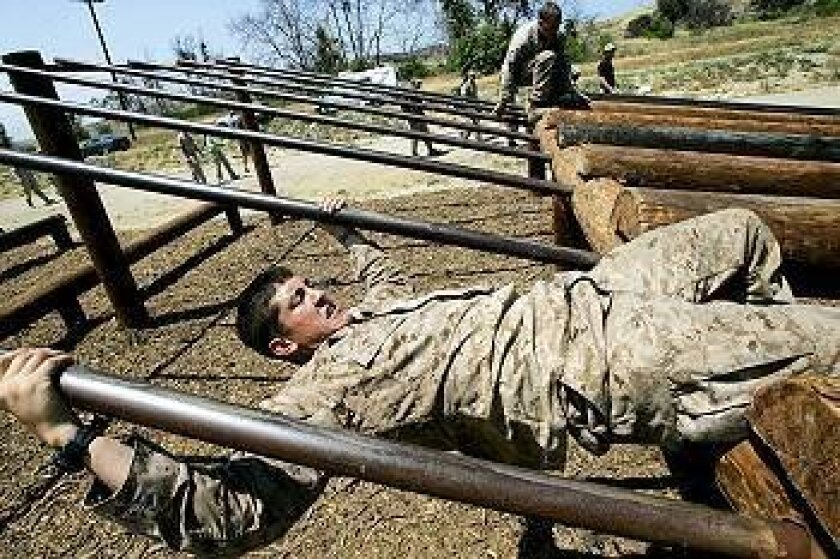 Second-place team Sgt. Caleb Medley (left) and Mark Rawson maneuver the obstacle course during the 22-mile, first-ever Marine Recon Challenge Saturday at Camp Pendleton. The course took contestants up to 15 hours.