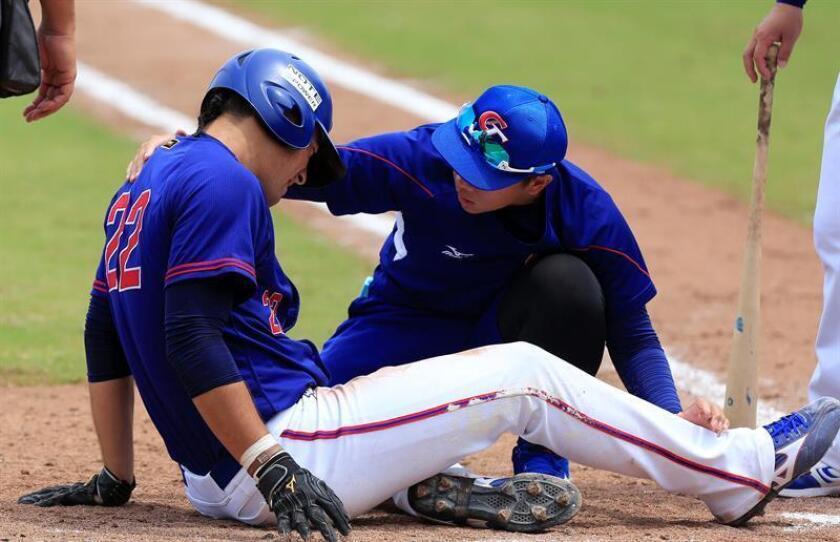Un médico asiste al jugador de China Taipei An-Ko Lin (i) hoy, viernes 19 de octubre de 2018, durante el juego entre las selecciones de México y China Taipei por la Copa Mundial de Béisbol Sub-23 que se disputa en Barranquilla (Colombia). EFE