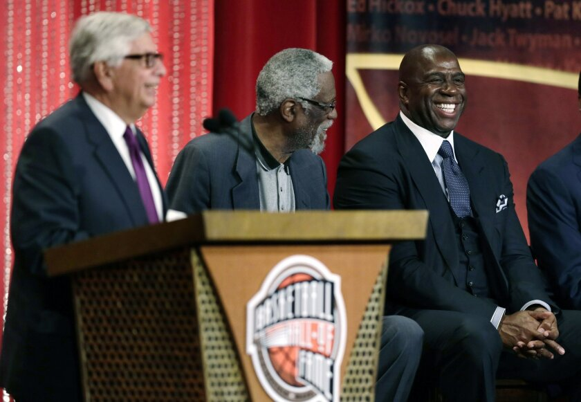 "Earvin ""Magic"" Johnson, right, smiles as he is mentioned by former NBA Commissioner David Stern, during Stern's induction speech at the Basketball Hall of Fame in Springfield, Mass., Friday, Aug. 8, 2014. (AP Photo/Charles Krupa)"