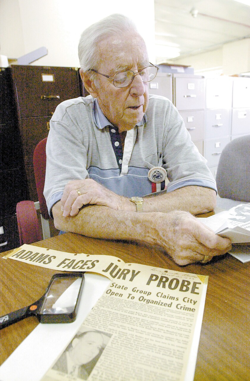 In this 2003 photo, retired Burbank Police Officer Harry Strickland looks over some news clippings from his career, as well as one involving Mickey Cohen and the Police Chief, Elmer Adams, who resigned amid allegations he was tied to Cohen and organized crime.