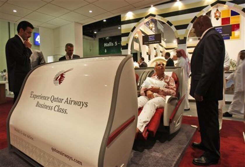 In this May 5, 2009 photo, a visitor examines the business class seat at the Qatar airline stand at Arabian Travel Market in Dubai, United Arab Emirates. Arab sheikdoms eager for higher regional and international profiles are ratcheting up their aviation race despite the global economic slump. (AP
