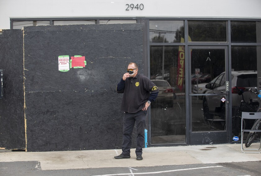 A guard stands outside an illegal dispensary at 2940 College Ave. in Costa Mesa raided by the Bureau of Cannabis Control.