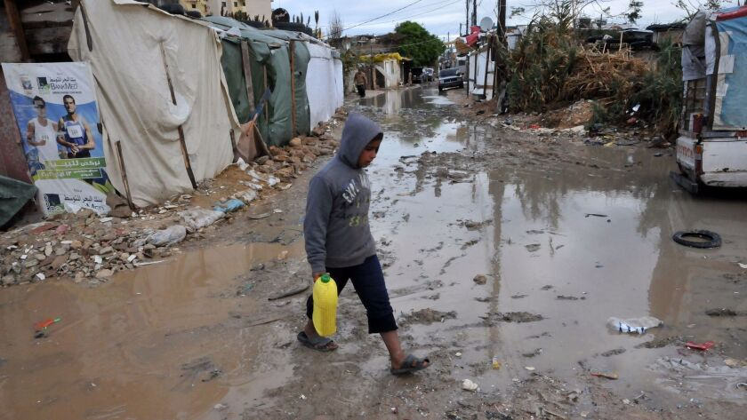 A Syrian refugee boy walks in a muddy alley at a makeshift camp near the northern city of Tripoli, Lebanon, in 2013.