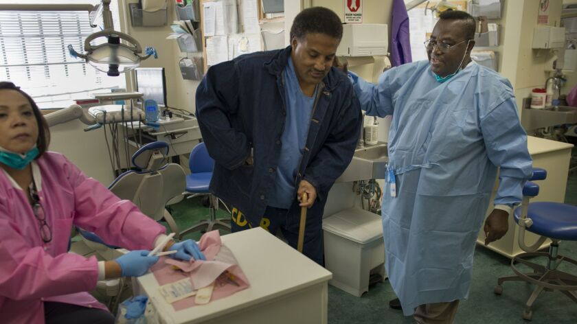 Dentist Opanin Gyaami treats inmate and patient Larry Butler in 2012 at the California medical facility in Vacaville.