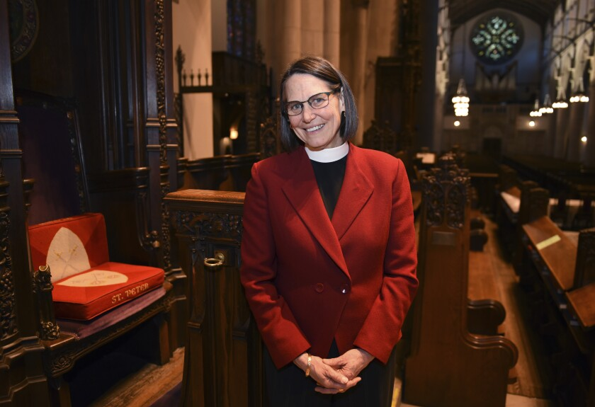 Bishop Bonnie Perry stands next to her chair in the Cathedral Church of St. Paul on Feb. 6, 2020 in Detroit. The Michigan diocese of the Episcopal Church has its first female and openly lesbian bishop. Perry was consecrated and ordained Saturday, Feb. 8, during a ceremony in Dearborn. (Clarence Tabb, Jr./Detroit News via AP)