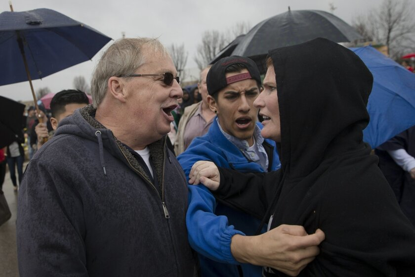 A Trump supporter, left, and a protester argue before Trump's arrival at a rally.