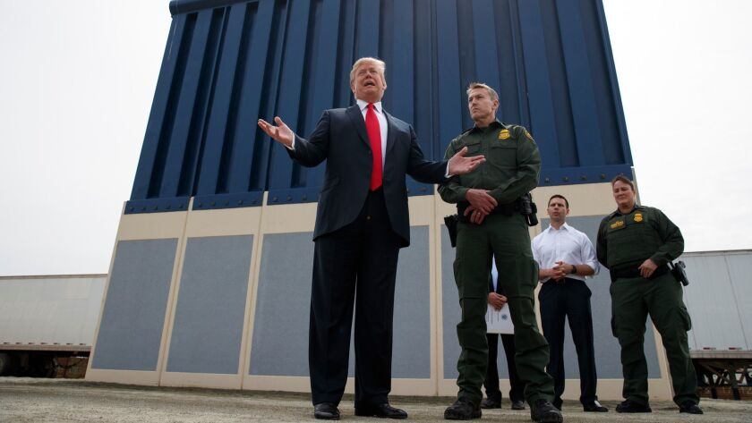 President Trump talks with reporters as he reviews border wall prototypes in San Diego on March 13.