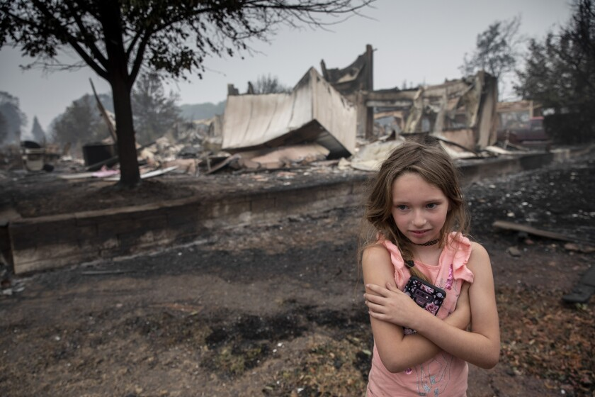 Ellie Owens, 8, looks at fire damage Friday as destructive wildfires devastate the region.