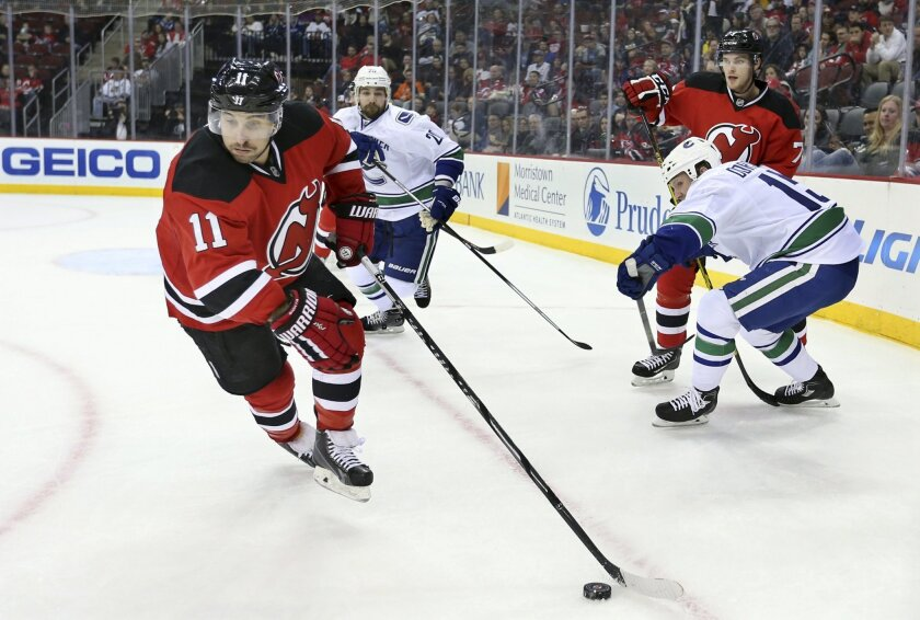 New Jersey Devils center Stephen Gionta (11) controls the puck during the first period of an NHL hockey game against the Vancouver Canucks, Sunday, Nov. 8, 2015, Newark, N.J. (AP Photo/Mel Evans)