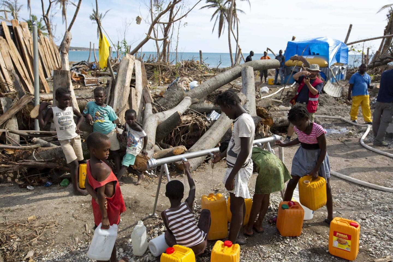 Varios niños recogen agua de un centro de distribución de un grupo de asistencia suizo en Les Cayes, Haití. Los pozos y las tuberías de las que la gente de esta península depende para el agua limpia fueron contaminados o dañados por la crecida del mar o por las aguas residuales desbordadas de las letrinas al aire libre que se usan habitualmente en las zonas rurales de Haití. (AP Photo/Dieu Nalio Chery)