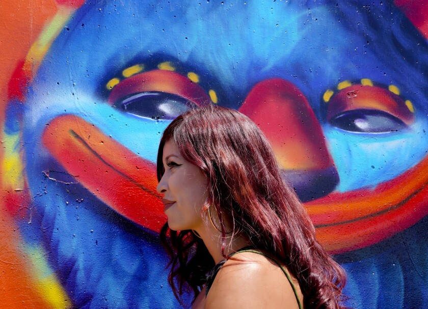 Local artist, Michelle Guerrero on August 19, 2019 stands next to a large wall mural that she painted in Chula Vista.