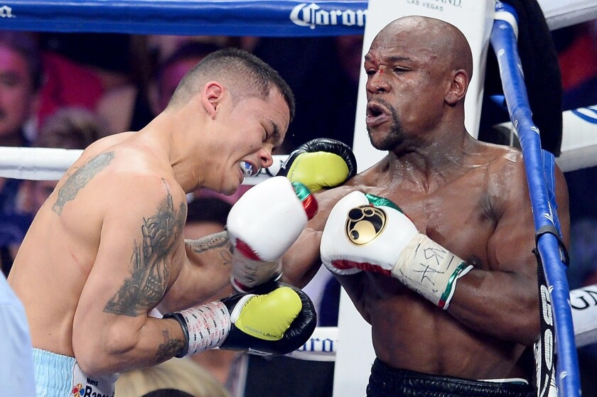 Floyd Mayweather Jr., right, throws a right punch to the face of Marcos Maidana during their welterweight unification title fight in Las Vegas on Saturday night.